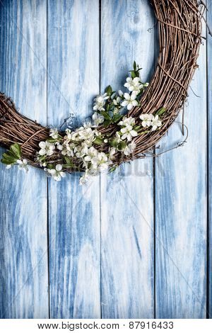 Wooden garland covered with spring apple blossom hanging on wooden door
