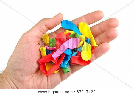 Hand holding a bunch of not inflated or deflated balloons isolated on white background
