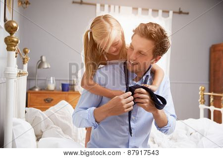 Daughter Helping Father To Get Dressed For Work