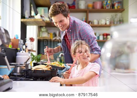 Daughter Helping Father To Cook Meal In Kitchen