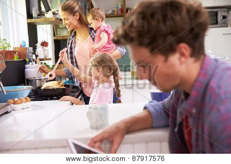 Mother Cooks Family Meal Whilst Father Uses Digital Tablet