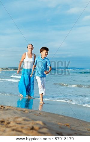 Happy mather and son running along the sea