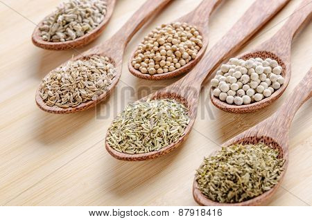 spoons of spices on cutting board