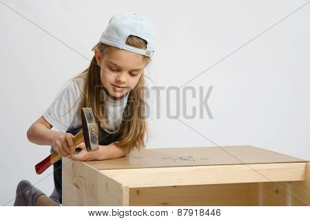 Girl In Classroom Work To Hammer Nail With A Hammer