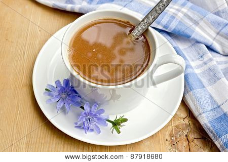 Chicory drink in white cup with spoon on board