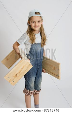 Portrait Of A Six Year Old Girl With Boards In Hands