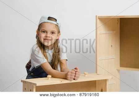 Girl Sitting With An Assembled Frame And Chest Wooden Box