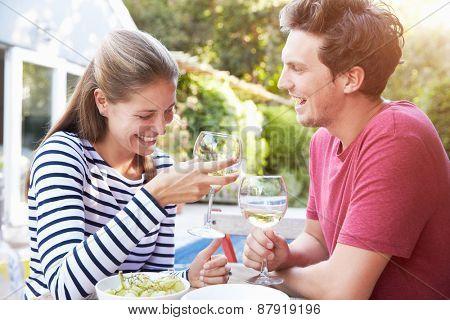 Couple Enjoying Outdoor Drinks In Garden