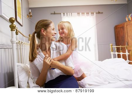 Daughter Hugging Mother As She Gets Dressed For Work