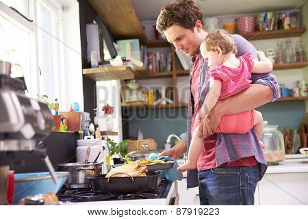 Father Cooking Meal Whilst Holding Daughter In Kitchen