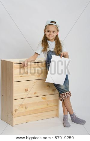 Girl In Overalls Collector Furniture Near Chest With A Sheet Of Paper