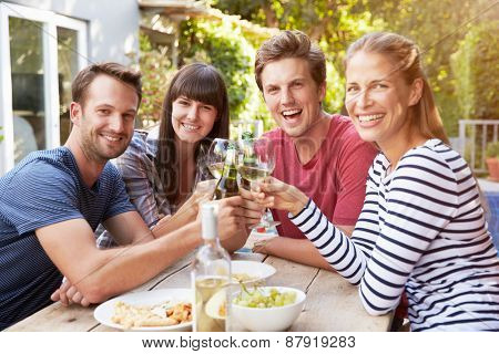Group Of Friends Enjoying Outdoor Drinks In Garden