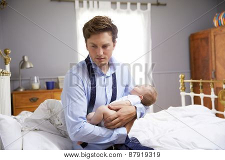 Stressed Father Dressed For Work Holding Baby In Bedroom