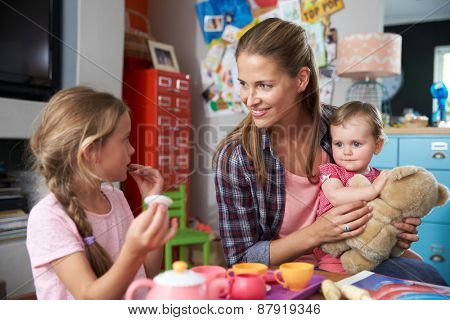 Mother Playing Game With Children And Toys In Bedroom