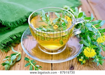 Herbal tea in cup with Rhodiola rosea and napkin on board
