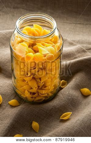 Shell macaroni pasta in glass bowl on hessian fabric cloth background