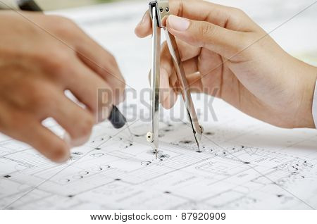 Macro of hands on blueprint