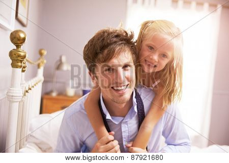 Daughter Hugging Father As He Gets Dressed For Work