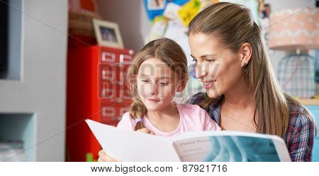 Mother Reading Book With Daughter In Bedroom