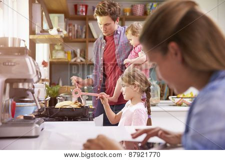 Father Cooks Family Meal Whilst Mother Uses Digital Tablet