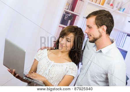 young casual attractive couple using laptop