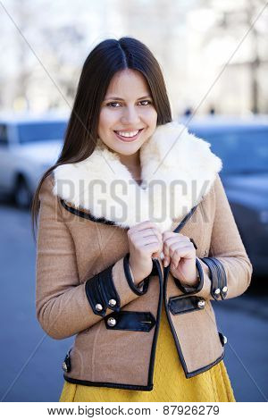 Portrait of a happy young girl in sheepskin coat on a background of the city