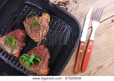 roast bloody beef fillet steaks on black teflon grill plate on wood