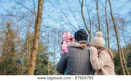 Couple with her little daughter enjoying of forest landscape