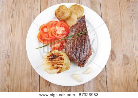meat food : roasted fillet mignon on white plate with tomatoes and chives served on wooden table