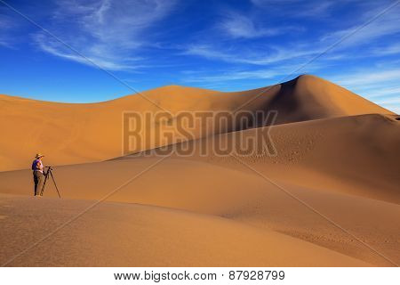 Sunrise in the orange sands of the desert Mesquite Flat, USA. Woman - photographer in a striped T-shirt is ready to shoot with a tripod among the sand dunes