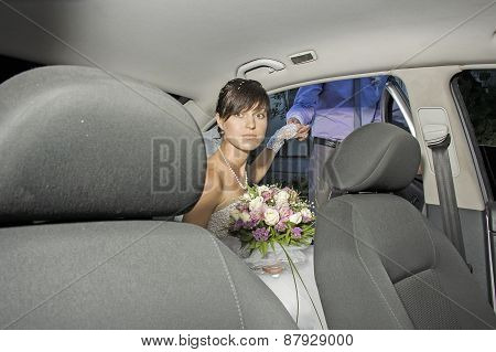 Young brunette bride posing for the camera in the car