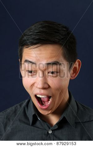 Young Asian man crying and looking down