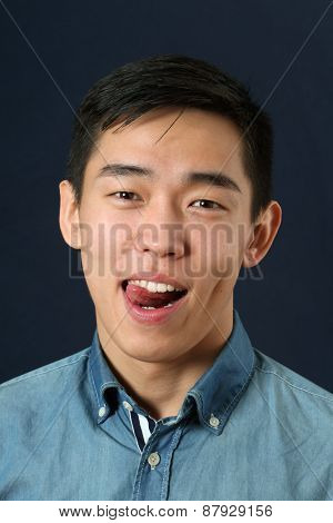 Pleased young Asian man showing his tongue and looking at camera