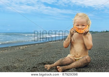 Little Cute Girl On The Sea Beach Eating Ripe Papaya