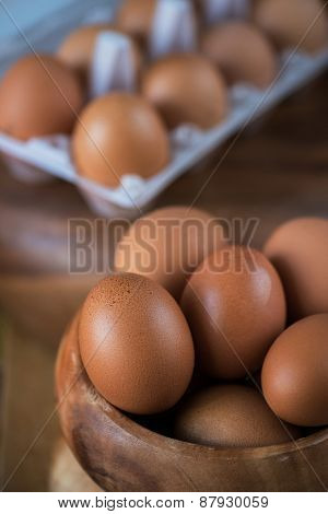 Fresh eggs at wooden plate closeup