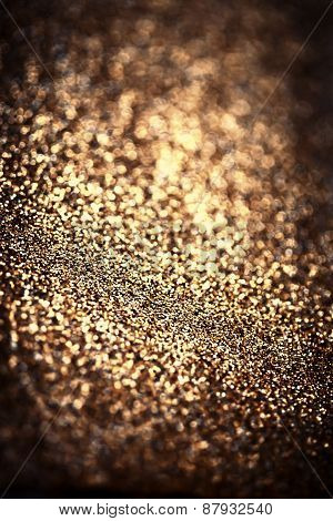 Holiday Abstract Glitter Background With Blinking Lights And Gold Defocused Texture. Golden Glitter