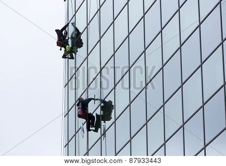 Sanitation Workers Cleaning Glass Facade Hotel