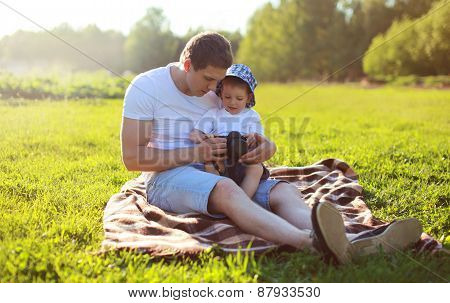 Life Portrait Of Father And Son Sitting Together On The Grass In Summer Evening Sunset, Dad And Chil