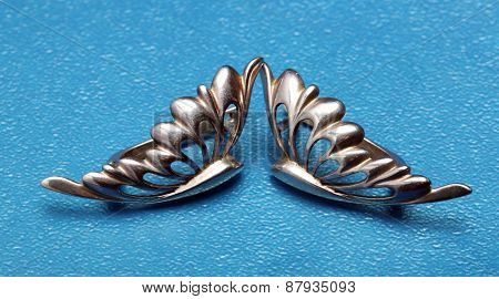 Silver Earring As Butterfly Wings On Blue