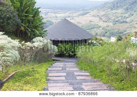 Round wooden roof hut house in the green hills background