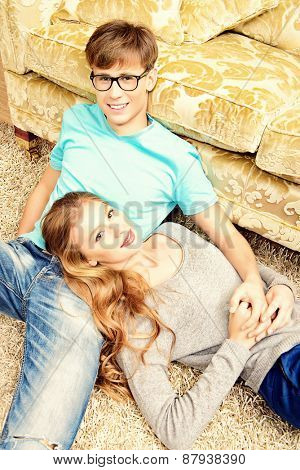 Beautiful young couple in love lying relaxed on a floor. They are in the cozy living room of their home.