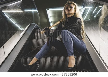 Sexy, Urban beautiful blonde with a baseball bat in escalators