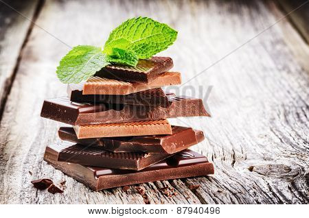 Stack Of Dark And Milk Chocolate Pieces With Mint Leaf