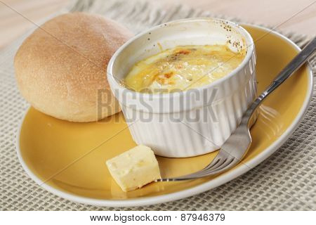 Breakfast with Swiss styled baked eggs, butter, and bun