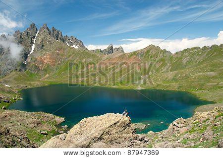 Man admiring a beautiful lake in the mountains