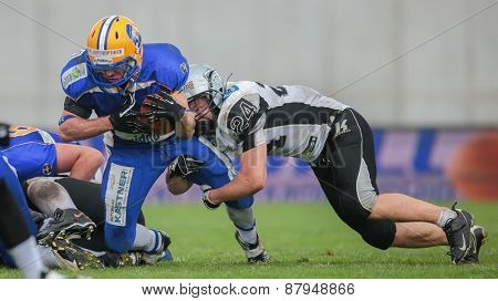 GRAZ, AUSTRIA - APRIL 26, 2014: RB Alexander Sanz (#1 Giants) is tackled by LB Fabian Seeber (#24 Raiders).