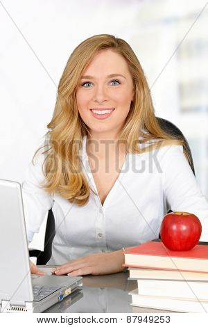 Young teacher with red apple sitting at desk