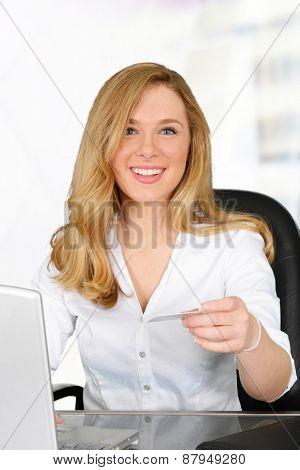 Woman sitting at computer looking at credit card