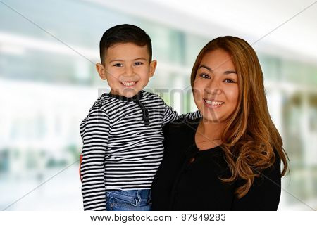 Happy young mother and son hugging and smiling