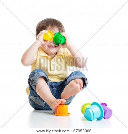 Little Child Is Playing With Toys While Sitting On Floor, Isolated Over White